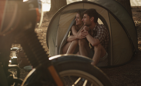 unworried: Affectionate young couple in tent LANG_EVOIMAGES