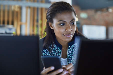 conveniences: Businesswoman texting at computer in office