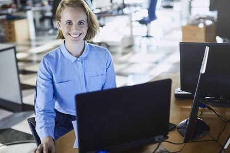 angled view: Portrait smiling businesswoman working at laptop in office