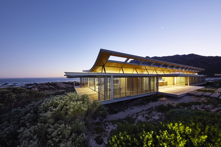 Illuminated modern luxury home showcase exterior with ocean view at dusk