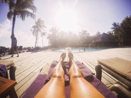 unworried: Woman sunbathing at sunny tropical poolside