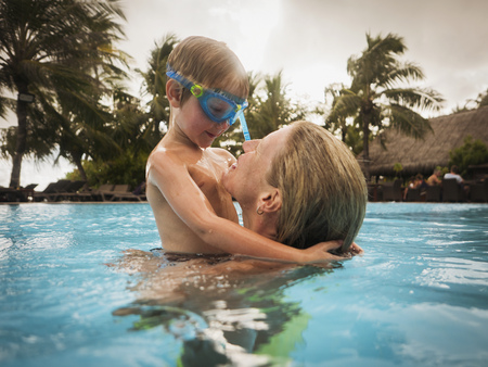 unworried: Mother and son hugging in swimming pool