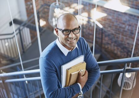 successfulness: Portrait confident businessman in stairway LANG_EVOIMAGES