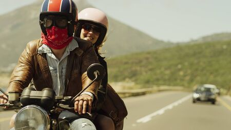 unworried: Young couple riding motorcycle on sunny road LANG_EVOIMAGES