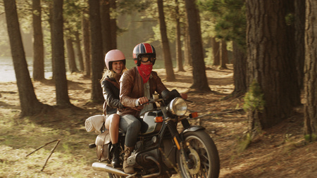 unworried: Young couple riding motorcycle in woods LANG_EVOIMAGES