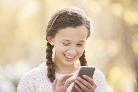 smile close up: Close up smiling girl texting with cell phone outdoors LANG_EVOIMAGES