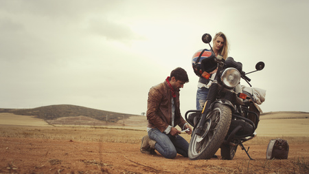 kneel down: Young couple repairing motorcycle in remote countryside field LANG_EVOIMAGES