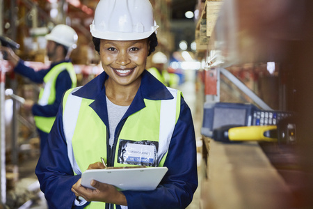 incidental people: Portrait smiling female worker with clipboard in distribution warehouse