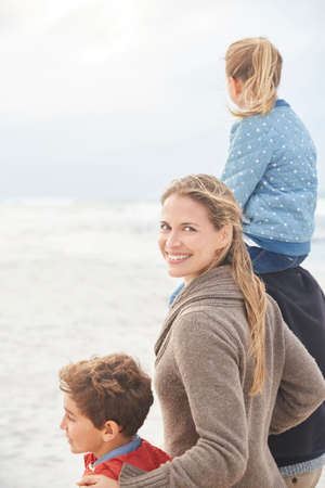 girls at the beach series: Portrait smiling family walking on winter beach