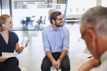 Business people smiling and listening in meeting
