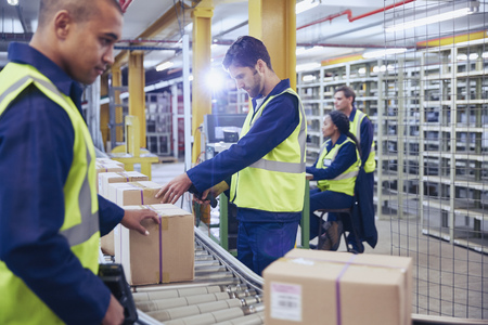 Workers scanning and processing boxes on conveyor belt in distribution warehouse