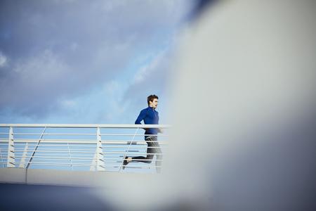 Male runner running on sunny footbridge