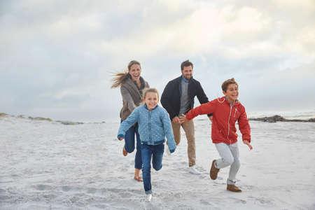girls at the beach series: Playful family running on winter beach