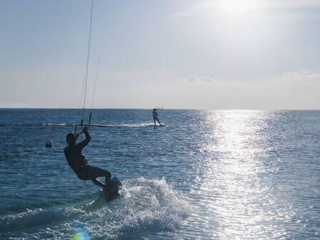 unworried: Parasailing on ocean under sunny blue sky LANG_EVOIMAGES