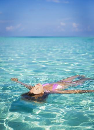 Serene woman floating in tropical ocean