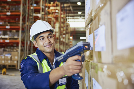 Worker with scanner scanning boxes in distribution warehouse