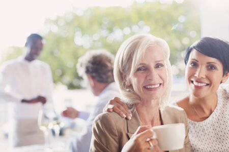 smile close up: Portrait smiling mother and daughter drinking coffee in restaurant LANG_EVOIMAGES