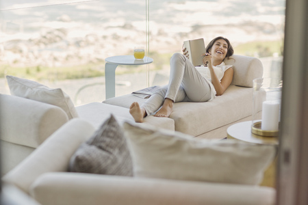 Smiling woman reading book relaxing on chaise lounge : reading chaise - Sectionals, Sofas & Couches
