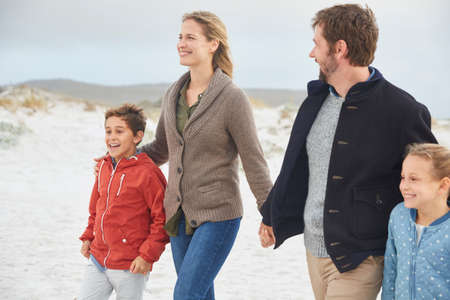 girls at the beach series: Family holding hands walking on winter beach