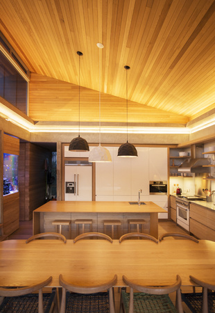 Illuminated slanted wood ceiling over luxury kitchen and dining table