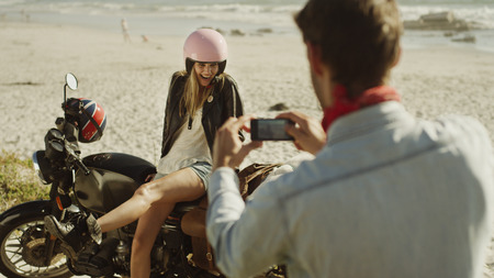 unworried: Young man photographing woman on motorcycle at beach