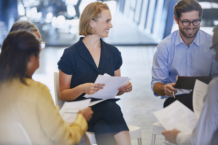 strategizing: Smiling business people discussing paperwork in meeting