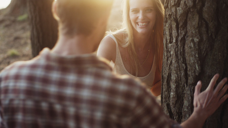 selectively: Playful couple at tree in woods