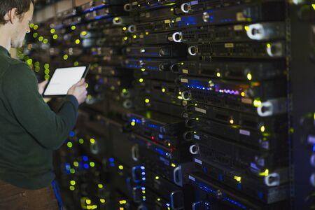 Server room technician using digital tablet at panel