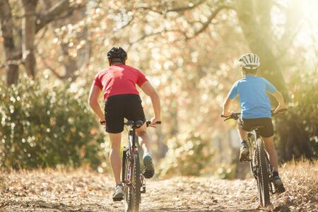 Father and son mountain biking on path in woods LANG_EVOIMAGES