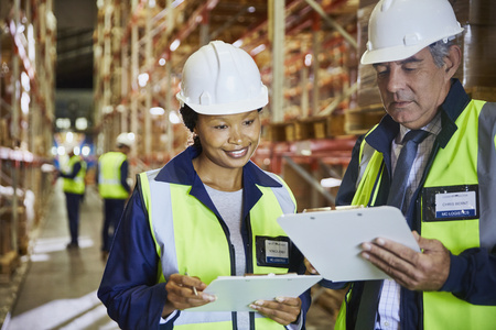 incidental people: Manager and worker with clipboards meeting in distribution warehouse