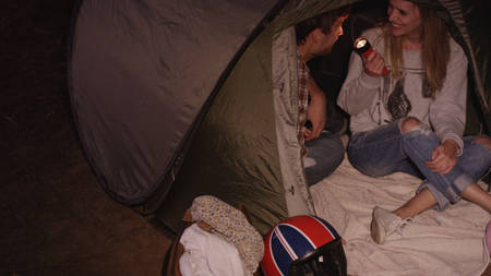 another way: Young couple with flashlight inside camping tent