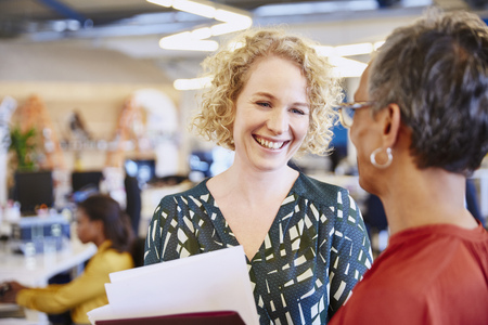 selectively: Smiling businesswomen talking in office