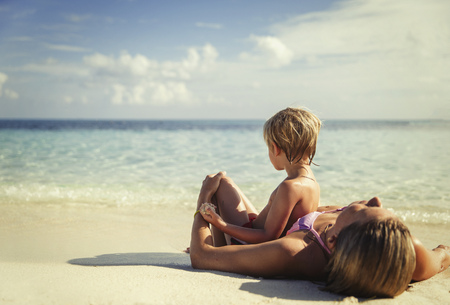 Mother and son laying and relaxing on tropical beach LANG_EVOIMAGES