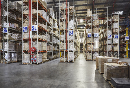 Merchandise stacked on shelves in labeled aisles in distribution warehouse