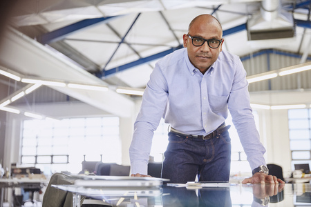 successfulness: Portrait serious businessman leaning on conference room table