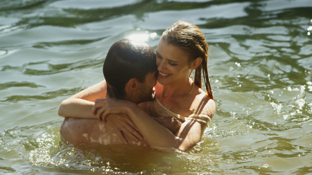 to get warm: Affectionate couple hugging and swimming in sunny lake
