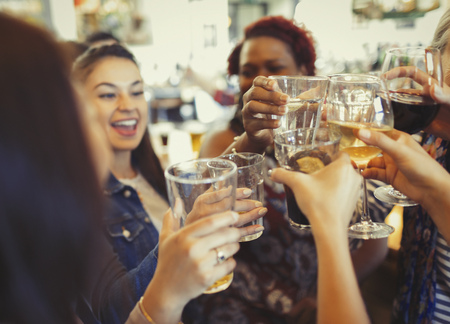 alcohol series: Enthusiastic women celebrating, toasting beer and wine glasses at bar