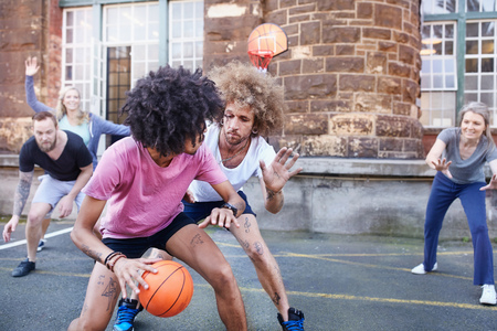 leaning over: Friends playing basketball on urban basketball court