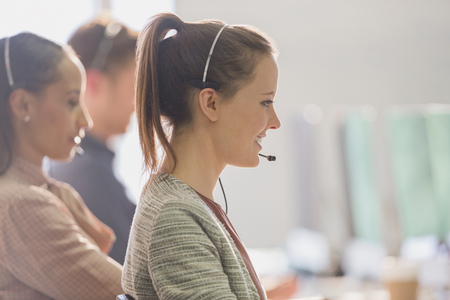 handsfree telephone: Smiling female telemarketer wearing headset talking on telephone in office LANG_EVOIMAGES