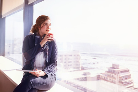 leaning over: Pensive businesswoman with digital tablet drinking coffee at sunny urban window