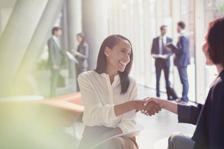 Smiling businesswomen handshaking in office lobby LANG_EVOIMAGES