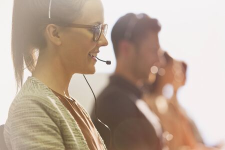 tele up: Close up female telemarketer wearing headset talking on telephone in office LANG_EVOIMAGES