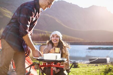 sit down: Young couple camping, cooking at camping stove at sunny lakeside LANG_EVOIMAGES