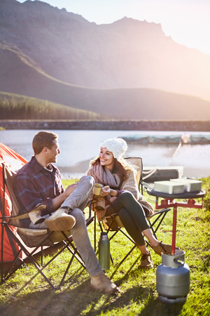 insulated: Young couple camping, drinking coffee at sunny lakeside campsite LANG_EVOIMAGES