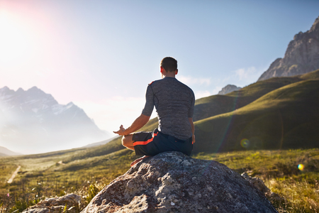 gyan: Young man meditating on rock in sunny, remote valley