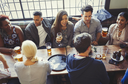 angle bar: Overhead view of friends drinking beer and wine at table in bar