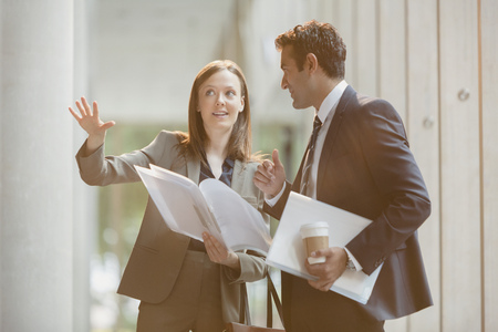 envisioning: Businesswoman explaining paperwork to businessman in office lobby LANG_EVOIMAGES