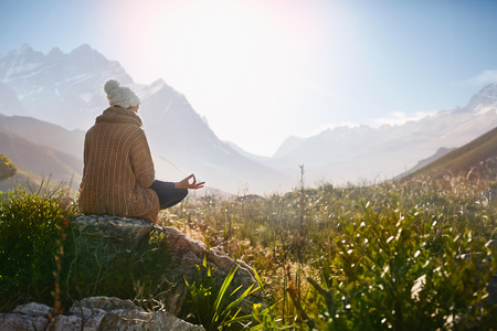 gyan: Young woman meditating on rock in sunny, remote valley