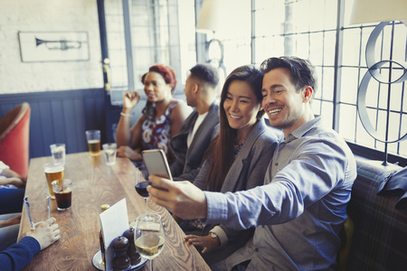 alcohol series: Smiling couple taking selfie with camera phone at table in bar