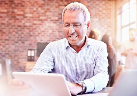 Smiling businessman using digital tablet in office